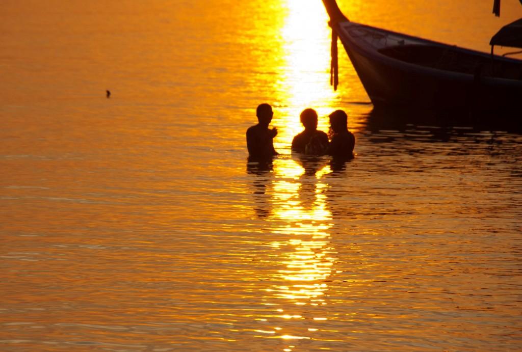 Photo de gens en train de se baigner à l'heure du coucher de soleil